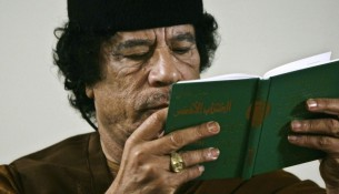 """FILE - In this Friday, March 2, 2007 file photo, Libya's Moammar Gadhafi holds a copy of the Green Book during a debate on the sidelines of celebrations marking the 30-year anniversary of the declaration of the """"jamahiriya,"""" or """"rule of the masses"""", in Sabha, Libya.  A new law that excludes former officials of the Moammar Gadhafi era from public office is dividing Libya and deepening the turmoil that has plagued the country since the civil war that ousted the erratic leader. Passed by lawmakers essentially at gunpoint, it bans not just those who held office but even clerics who glorified the dictator and researchers who worked on his notorious political tract, the Green Book. (AP Photo/Nasser Nasser, File)"""