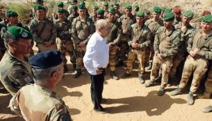 "France's minister of defence Jean-Yves Le Drian (C) speaks to French troops in the northern Malian region of Ifoghas on March 7, 2013.  The ministry said Le Drian started his visit in the Amettetai valley in the Ifoghas mountains, where French and Chadian troops have been hunting down rebels driven from northern Mali's main cities by a lightning intervention launched in mid-January.  AFP PHOTO / EMA-ECPAD /  ARNAUD ROINE  RESTRICTED TO EDITORIAL USE - MANDATORY CREDIT ""AFP PHOTO / EMA-ECPAD / ARNAUD ROINE "" - NO MARKETING NO ADVERTISING CAMPAIGNS NO ARCHIVES - DISTRIBUTED AS A SERVICE TO CLIENTS - TO BE USED WITHIN 30 DAYS FROM MARCH 7, 2013"