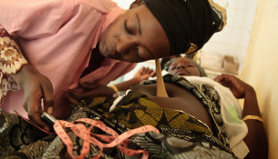 A midwife listens for heartbeat on the belly of Mariam Moutari, 20, who is 8 month pregnant with her second child, during a pre-natal consutlation at the Bilmari health center in the town of Mirriah, Niger on Wednesday March 21, 2012.